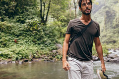 Young man crossing the stream Royalty Free Stock Images