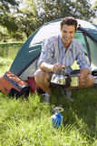 Young man crouching beside dome tent in woodland clearing, taking boiled kettle from camping stove, smiling, portrait Royalty Free Stock Photography