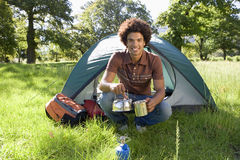 Young man crouching beside dome tent in woodland clearing, taking boiled kettle from camping stove, smiling, portrait Stock Photos