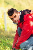 Young man crouching down in red jacket covered with beautiful sh Royalty Free Stock Photos