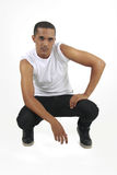 Young man crouching staring at a subject. Young mixed race male wearing a white short sleeve shirt and black jeans on an isolated background staring at a subject Stock Photography