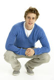 Young Man Crouching In Studio Stock Image