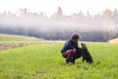 Young man crouching to pet his black dog in a beautiful green me. Adow with white mist above them and forest in background Stock Image