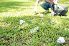 Young man crouching to waste and picking it up in bin bag Stock Images