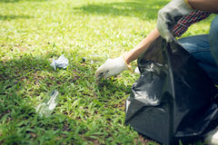 Young man crouching to waste and picking it up in bin bag Royalty Free Stock Photography
