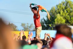 Young man from the crowd cheering, with an Irish flag, at FIB Festival Royalty Free Stock Image