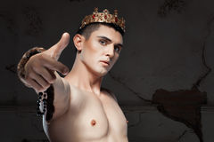 Young man with crown on the head pointing her finger. Royalty Free Stock Photography