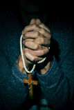 Young man with a crucifix in his hands Stock Photos