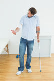 Young man with crutch and bandaged hand Stock Image