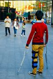 A young man on crutches looks at a happy family stock image