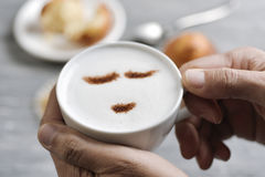 Young man with a cup of cappuccino. Closeup of a young caucasian man holding a cup of cappuccino with a happy face drawn with cocoa powder on the milk foam, on a Royalty Free Stock Photos