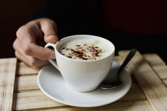 Young man with a cup of cappuccino. Closeup of a young caucasian man about to drink a cup of cappuccino, sitting at a rustic wooden table royalty free stock images