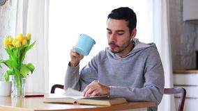 Man with cup of drink reading a book at kitchen stock video