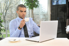 Young man with cup and laptop in restaurant. Stock Photo