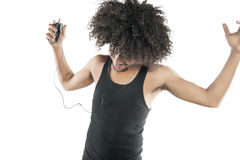 Young man with curly hair enjoying while listening to mp3 player over white background Stock Photo