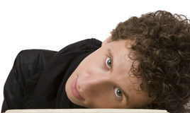 The young man with curly hair has bent to a table Stock Photo