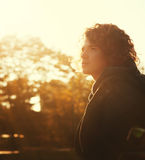 Young man with curly hair portrait in autumn park at a sunset. Stock Photos