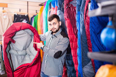 Young man customer choosing new sleeping bag in store. Young man customer choosing new sleeping bag in sports equipment shop Royalty Free Stock Photo