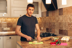 Young man cuts bread baguettes in the kitchen Royalty Free Stock Images