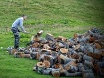 Young man that cuts the firewood with an axe in Montenegro. royalty free stock photos