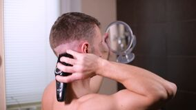 A young man cuts himself, using reflection mirrors and a hair clipper