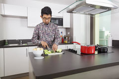 Young man cutting broccoli at kitchen counter Stock Images