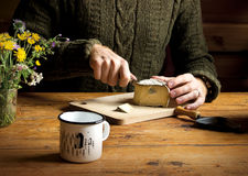 Young man is cutting cheese on wooden table. stock image
