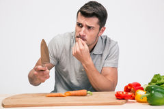 Young man cutting his finger with knife Stock Photo