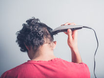 Young man cutting his hair at home Royalty Free Stock Image