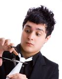 Young man cutting his tie. Young man in black shirt, white tie and scissors royalty free stock photos