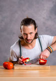 Young man cutting sweet pepper and looking angry Stock Photos