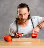 Young man cutting sweet pepper and looking angry Stock Image