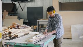 Young man cutting wooden plank with electric circular saw in workroom. Young man is cutting wooden plank with electric circular saw in workroom standing near stock footage