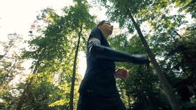 Young man cyborg jogs in the forest, wearing his special artificial hand. 4K. Young man jogs in the forest, wearing his special artificial hand