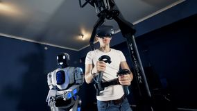 A young man and a cyborg are moving their hands and bodies in synch through virtual reality