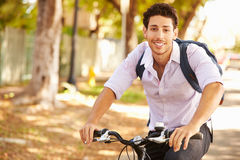 Young Man Cycling Along Street To Work Stock Image