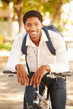 Young Man Cycling Along Street To Work Royalty Free Stock Photos