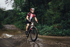 The young man cycling on mountain bike ride Cross-country Stock Image