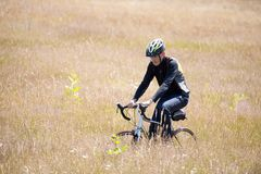 Young man cycling out on bike rides through the field Royalty Free Stock Photo