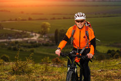 Young man cycling on a rural road through green meadow Stock Images