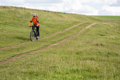 Young man cycling on a rural road through green meadow. Young man cycling on a rural road through green spring meadow during sunset Royalty Free Stock Photography