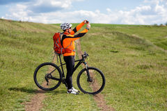 Young man cycling on a rural road through green meadow Royalty Free Stock Photos