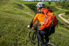 Young man cycling on a rural road through green meadow. Young man cycling on a rural road through green spring meadow during sunset Stock Photography