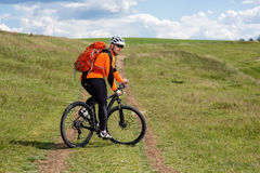 Young man cycling on a rural road through green meadow. Young man cycling on a rural road through green spring meadow during sunset Stock Photo