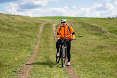 Young man cycling on a rural road through green meadow. Young man cycling on a rural road through green spring meadow during sunset Royalty Free Stock Images
