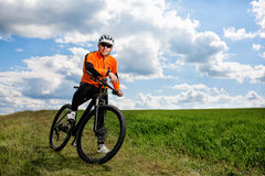 Young man cycling on a rural road through green meadow Stock Photography