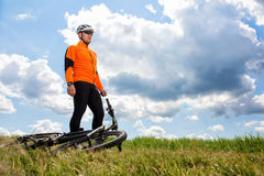 Young man cycling on a rural road through green meadow Royalty Free Stock Image