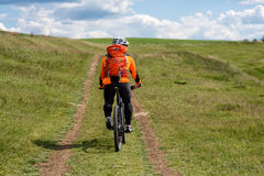 Young man cycling on a rural road through green meadow Royalty Free Stock Photography
