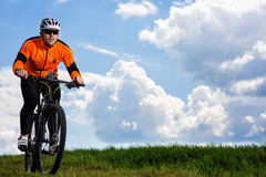 Young man cycling on a rural road through green meadow. Young man cycling on a rural road through green spring meadow during sunset Stock Photos