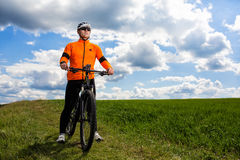 Young man cycling on a rural road through green meadow. Young man cycling on a rural road through green spring meadow during sunset Stock Image